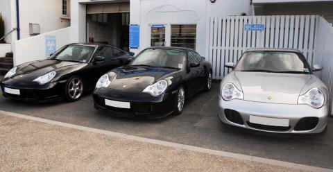 Three Porsche 911 turbos outside the devon garage