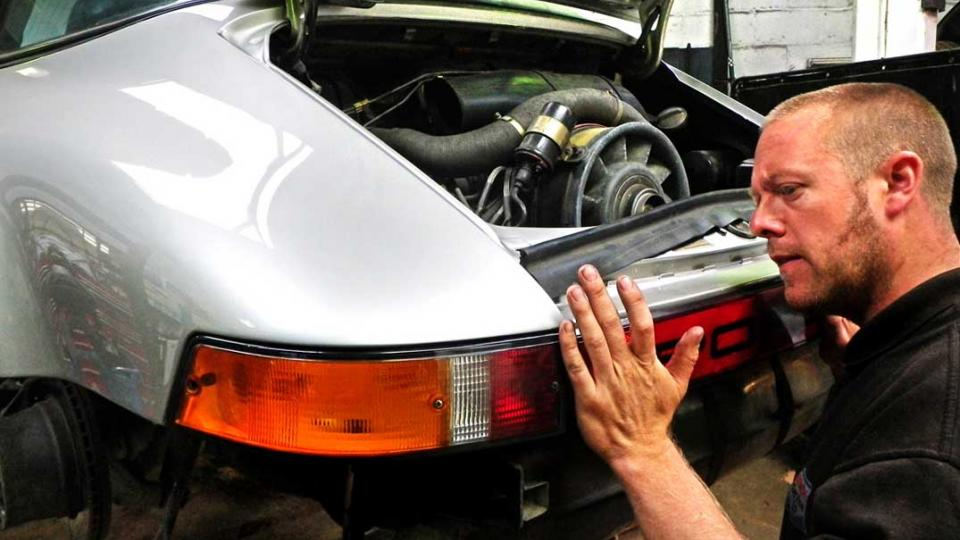 Dave refits the rear trim to a Porsche 911 after body work repair