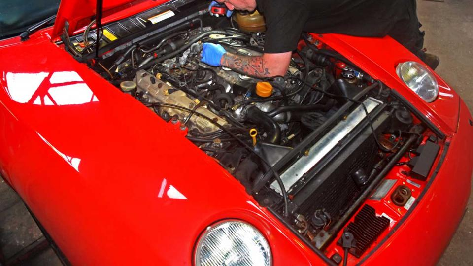 Matt inspects for leaking hoses on the Porsche 928