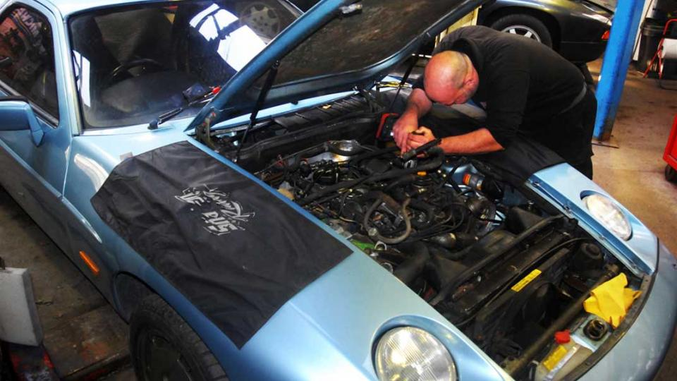 Ashley changes the spark plugs in a Porsche 928 S2