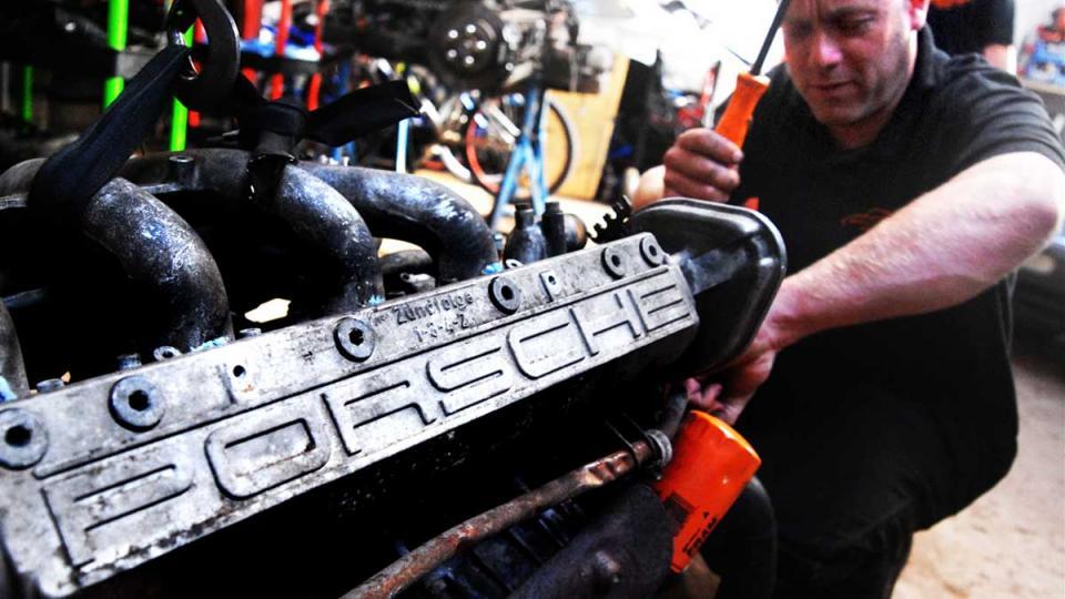 Dave works to refit the Porsche 944 engine after refurbishment