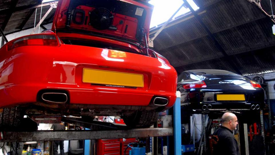 A pair of Porsche 996's on ramps ready for servicing to start