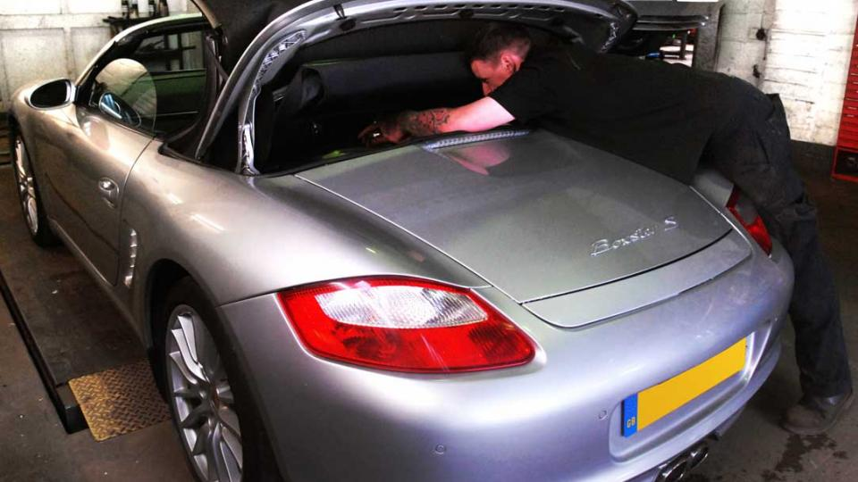 Placing the Boxster hood in the service position to allow access