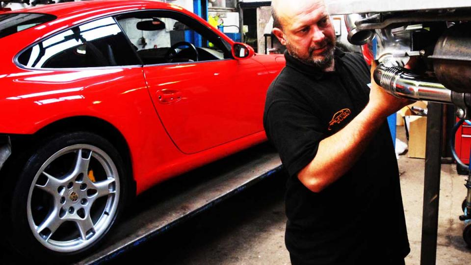 Ashley fits the rear exhaust to a Porsche 911 in North Devon