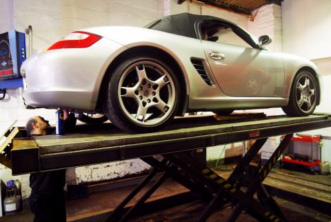 Inspecting the underside components and chassis of a Porsche Boxster 987