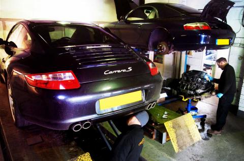 Two Porsche 911's on ramps for repair and inspection