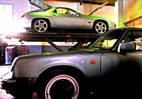 A silver Porsche 928 rides high in the Devon workshop for MOT test